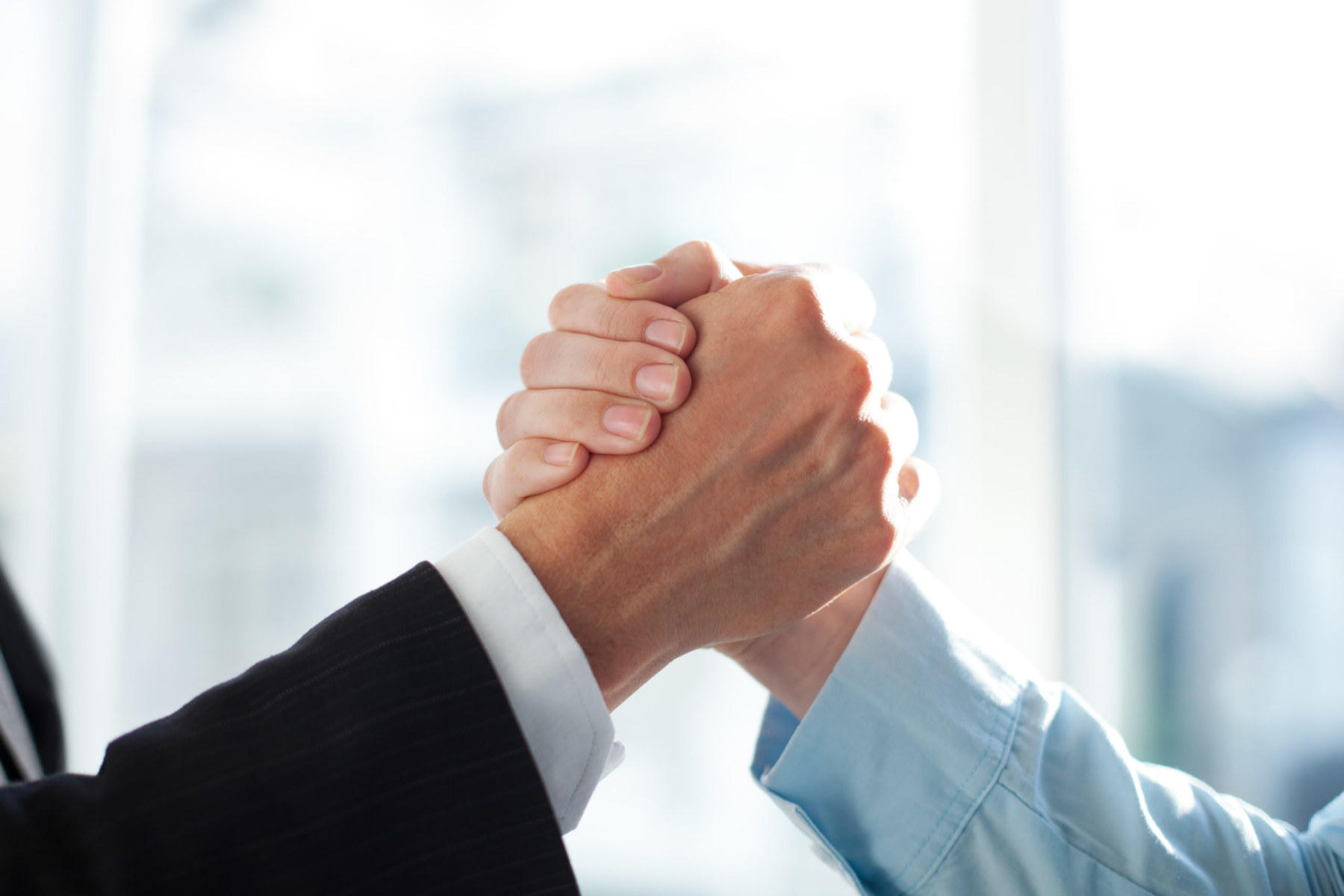 Close-up of two clasped hands of businessmen